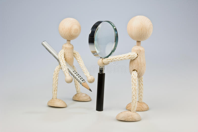 Job interview. A wooden doll looking through a magnifier to antother doll with pencil royalty free stock images