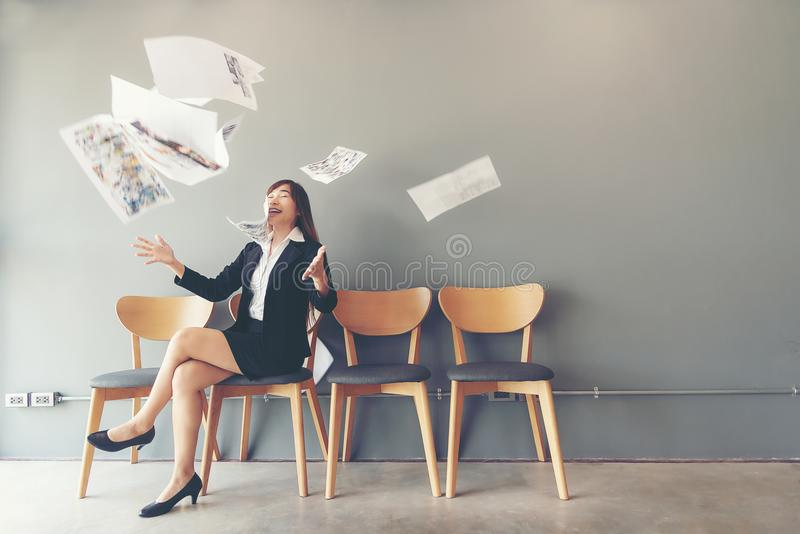Job Interview. Asian women tossing a bunch of papers celebrating the end of job interview. Job Interview. Asian woman tossing a bunch of papers celebrating the royalty free stock image