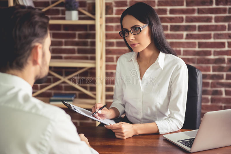 At the job interview. Beautiful female employer in suit is conducting a job interview while sitting in her office stock image