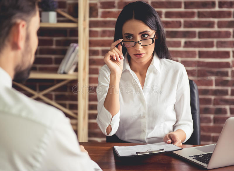 At the job interview. Beautiful female employer in suit is conducting a job interview while sitting in her office stock images