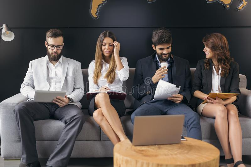 Job interview candidates. Lined up business people sitting in an office building waiting room, waiting for a job interview stock photo