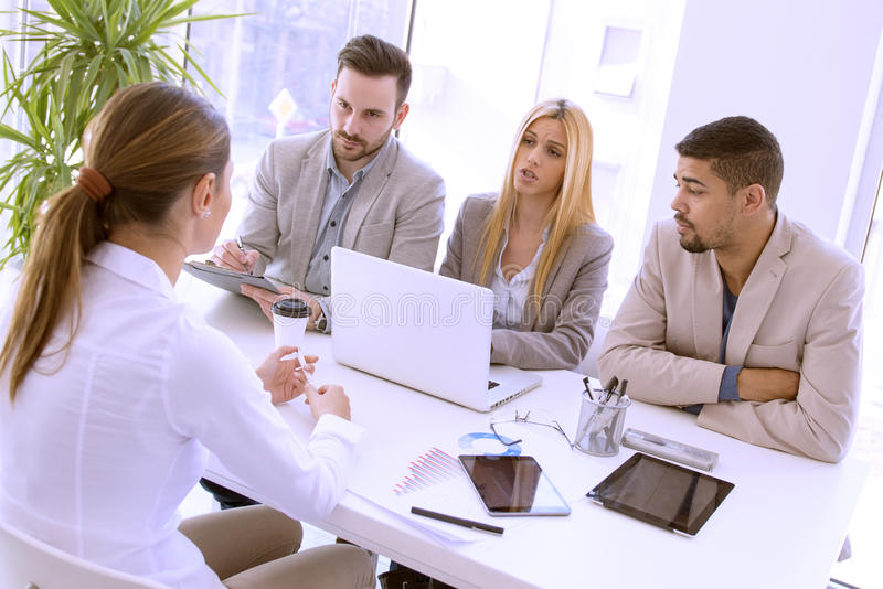 Job interview. Group of business people having job interview. They are communicating with female candidate stock image