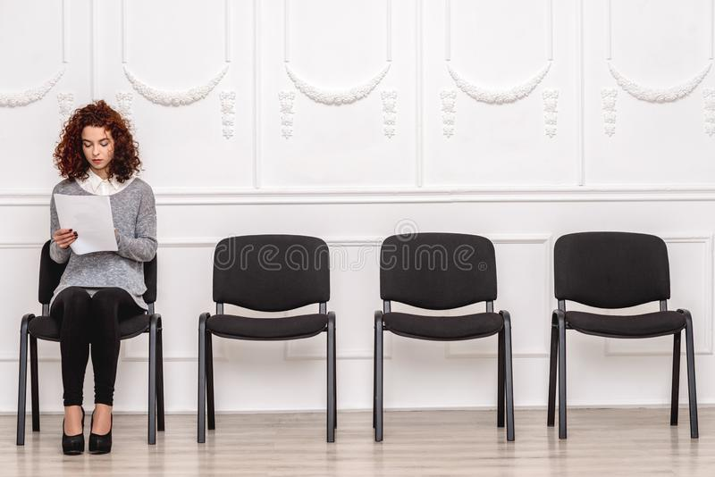 Job Interview. Woman sitting on chair  on white waiting checking resume concentrated stock image