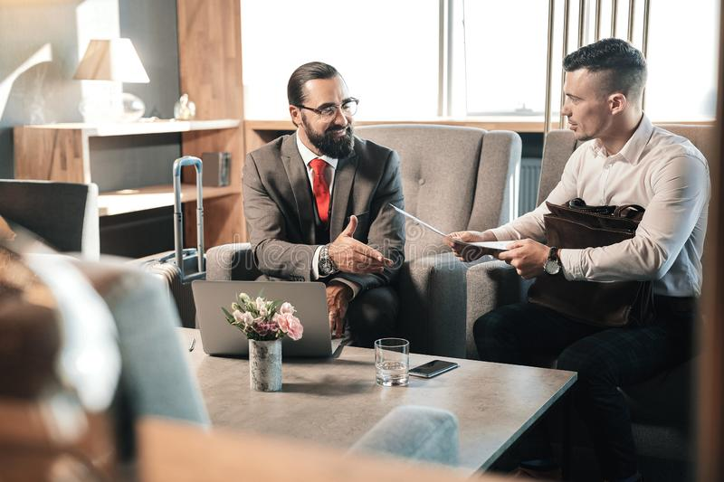 Young economist coming to job interview to famous businessman. Job interview. Young promising economist feeling curious while coming to job interview to famous royalty free stock image