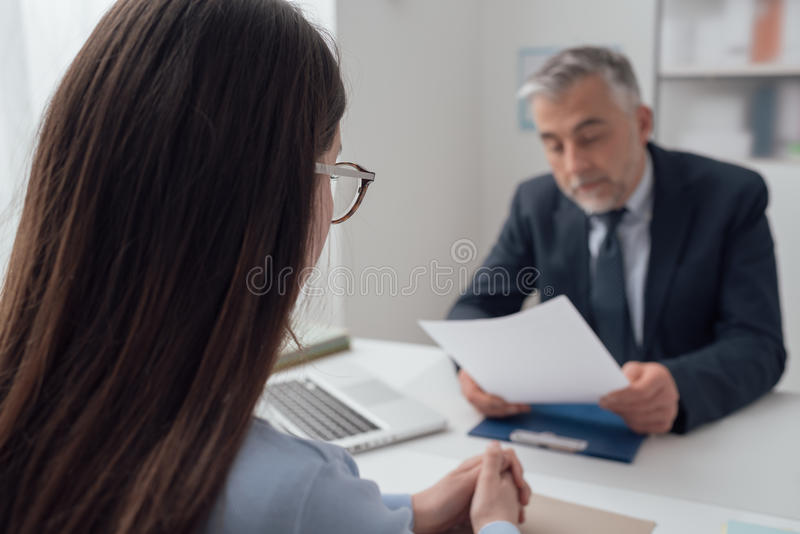 Job interview. Young women having a job interview with a corporate manager in his office, he is examining her resume stock images