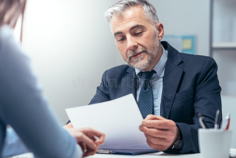 Job interview. Young women having a job interview with a corporate manager in his office, he is examining her resume stock image