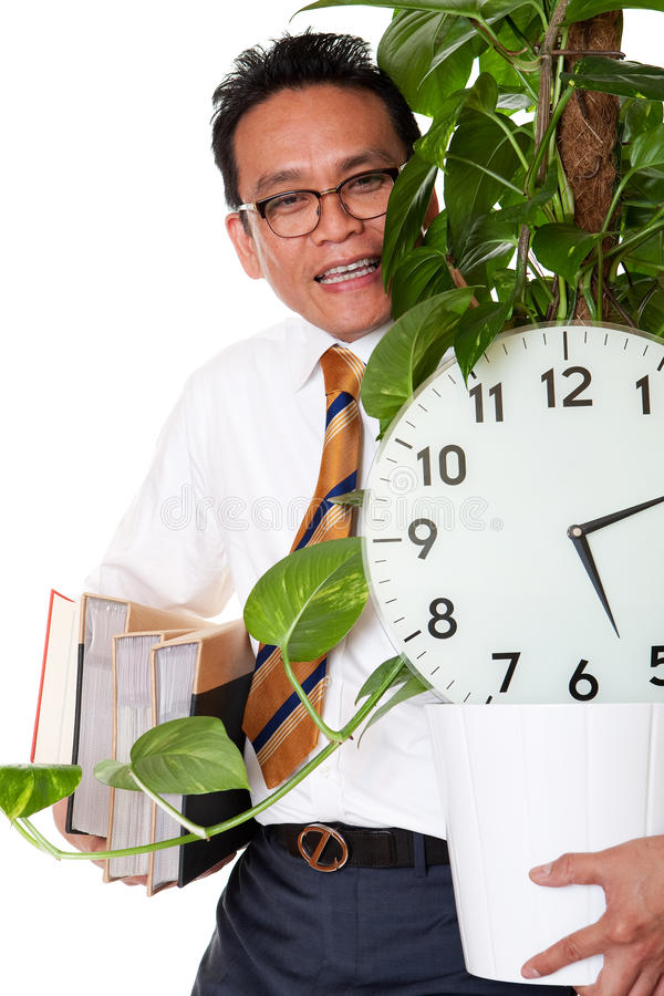 Job leave. Manager carry flowering pot plant, clock and acts before white background royalty free stock photos