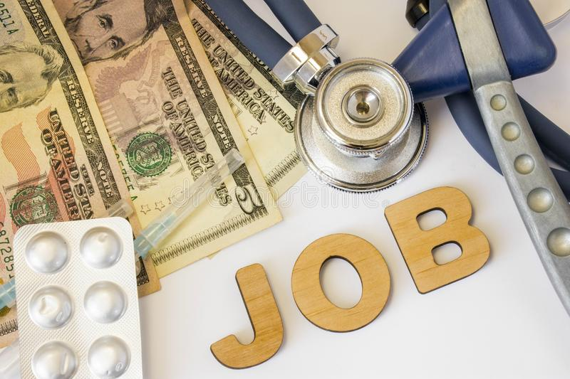 Job in medicine and pharmacy concept photo. Stethoscope, neurological reflex rubber hammer, dollar bills and syringe with medicine. Is near 3D letters job stock photo