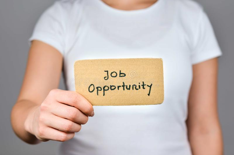 Job Opportunity  and Careers ads. Job Opportunity  phrase handwritten  on square  cardboard paper holding by young caucasian  women  in  right hand royalty free stock photography