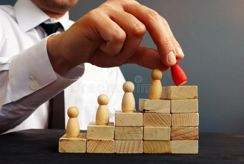 Job Promotion Manager hält Figürchen nahe Karriereleiter lizenzfreie stockfotos