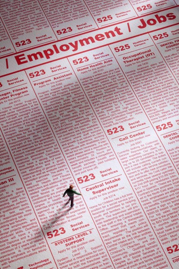 Job Search. Toy person seeking job employment in newspaper ads