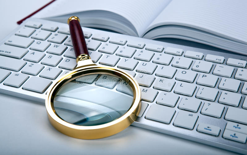 Job search on the Internet concept. Magnifier and computer keyboard on the desktop close up royalty free stock images