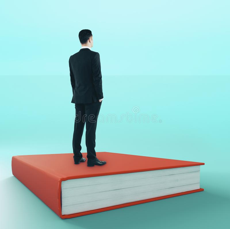 Job search and wisdom concept. Young businessman looking into the distance while standing on book. Job search and wisdom concept royalty free stock photos
