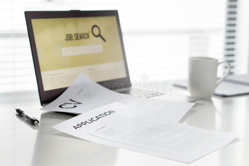 Job seeking in home office. Laptop with online search engine for work. Curriculum vitae or CV and application paper on table. royalty free stock images
