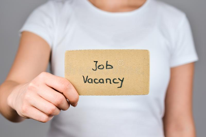 Job Vacancy and   Offers. Job Vacancy  phrase handwritten  on square  cardboard paper holding by young caucasian  women  in  right hand stock photo