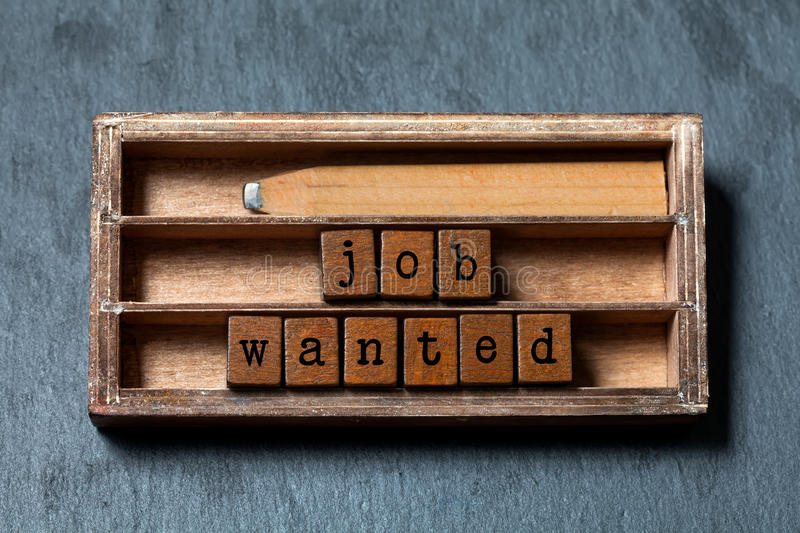 Job wanted phrase. Recruiting and work searching conceptual quote. Vintage box, wooden cubes with old style letters. Wood pencil. Gray stone textured royalty free stock photography