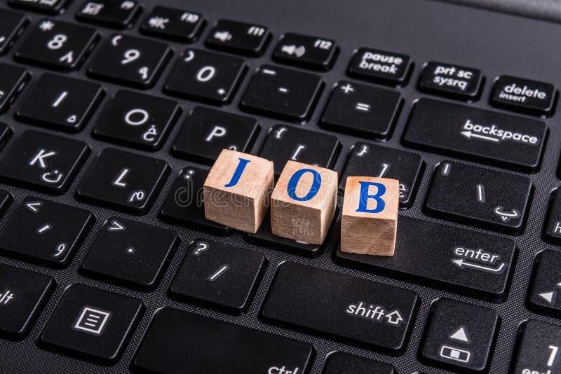 Job word on laptop. Wooden block with Job word on laptop keyboard. Online job concept royalty free stock photos