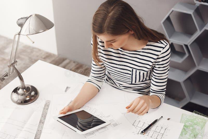 Jobb, karriär och affärsidé Stående av ungt trendigt yrkesmässigt kvinnligt märkes- sammanträde på tabellen som ser royaltyfria bilder