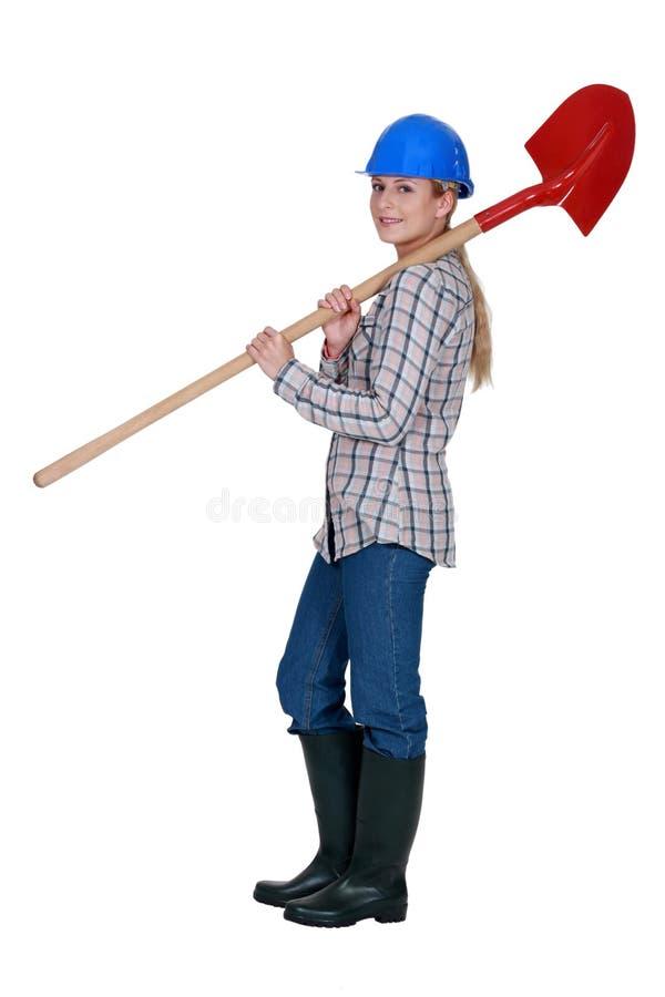Jobbare som bär en spade royaltyfri bild