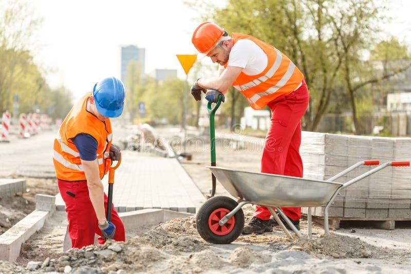 Jobbare som gräver på vägkonstruktion royaltyfri fotografi