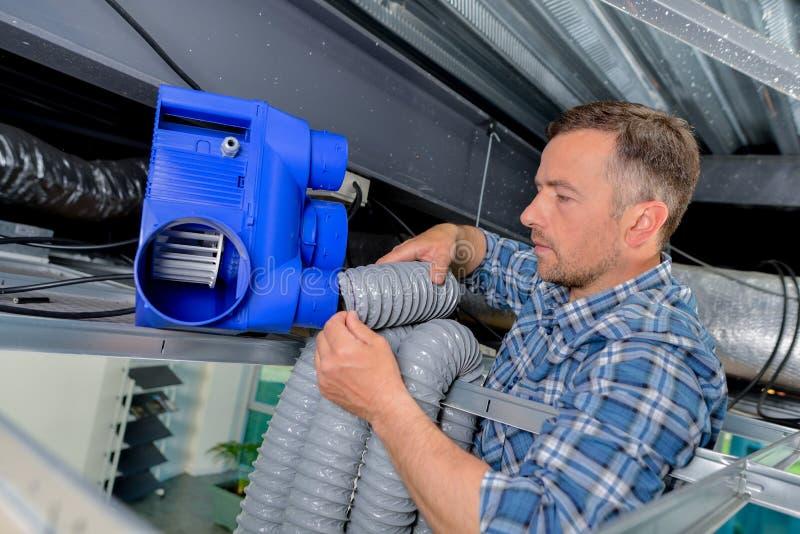 Jobbare som monterar tvungen ventilation arkivbild