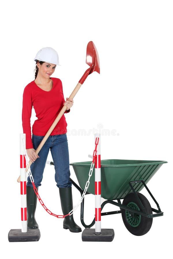Jobbare som rymmer en spade arkivfoton