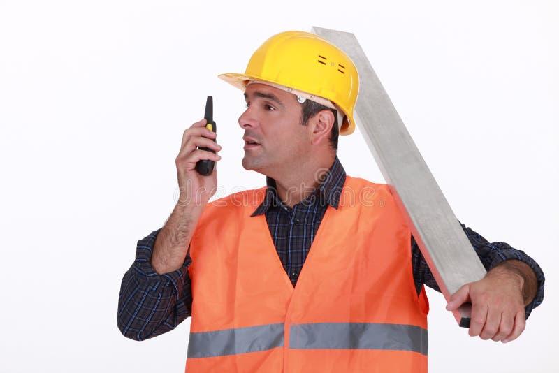 Jobbare som talar in i walkie-talkie royaltyfri bild