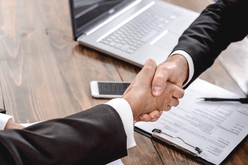 Jobbgranskning Arbetsgivare och kandidat som sitter i ämbetet skakar hand om avtal arkivfoton
