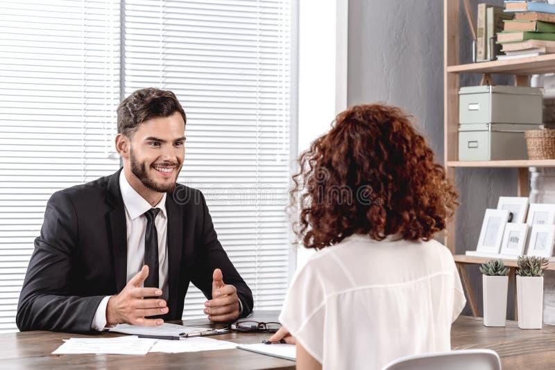 Jobbgranskning Arbetsgivare som talar med kandidat som leker det trevliga ämbetet fotografering för bildbyråer