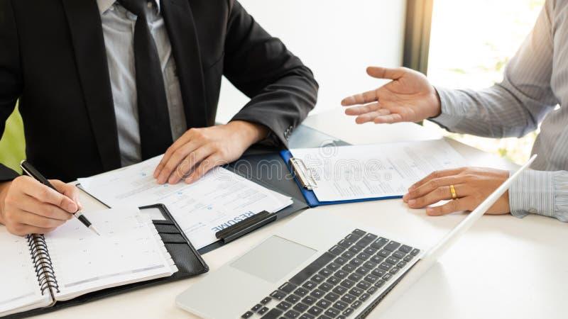 Jobbintervju och hyra den begrepps-, tidsbest?llningskandidataff?rsmannen som f?rklarar om hans profil, och svar till personalres arkivfoto