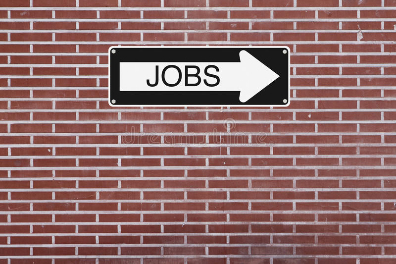 Jobs This Way. A modified one way sign mounted on a brick wall stock photos