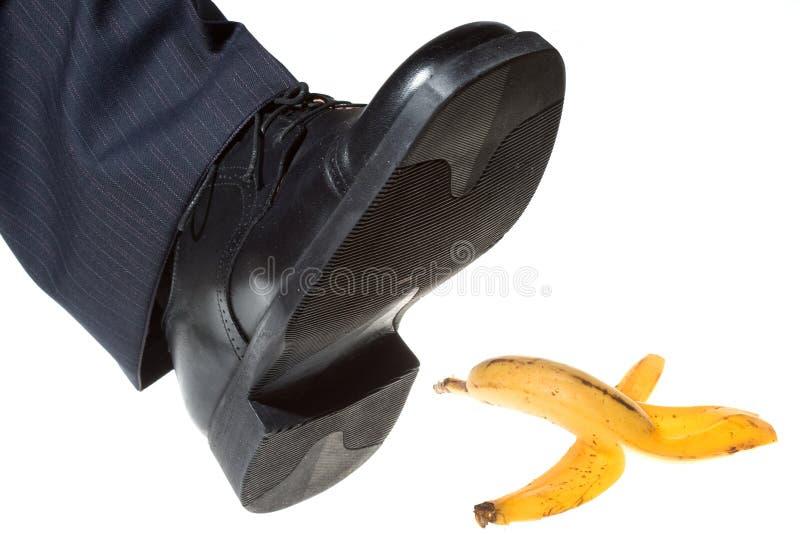 Jobstepp auf einer Bananenschale lizenzfreies stockbild