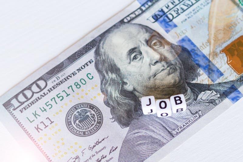 Jobwort mit weißen Buchstaben unter Bargelddollarbanknote auf hölzernem weißem Hintergrund Oben geschlossen Konzept der Gestalt e stockbild