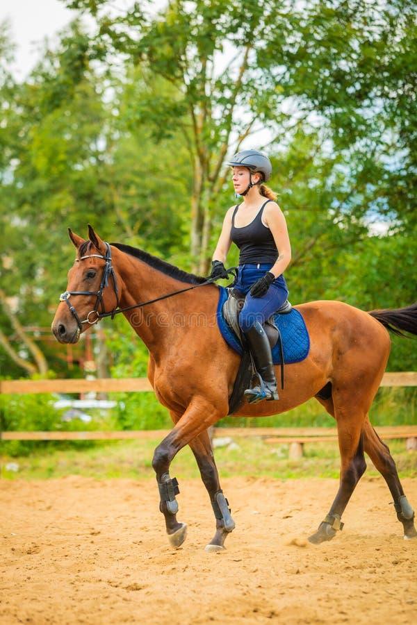 Jockey κορίτσι που κάνει την ιππασία στο λιβάδι επαρχίας στοκ εικόνες
