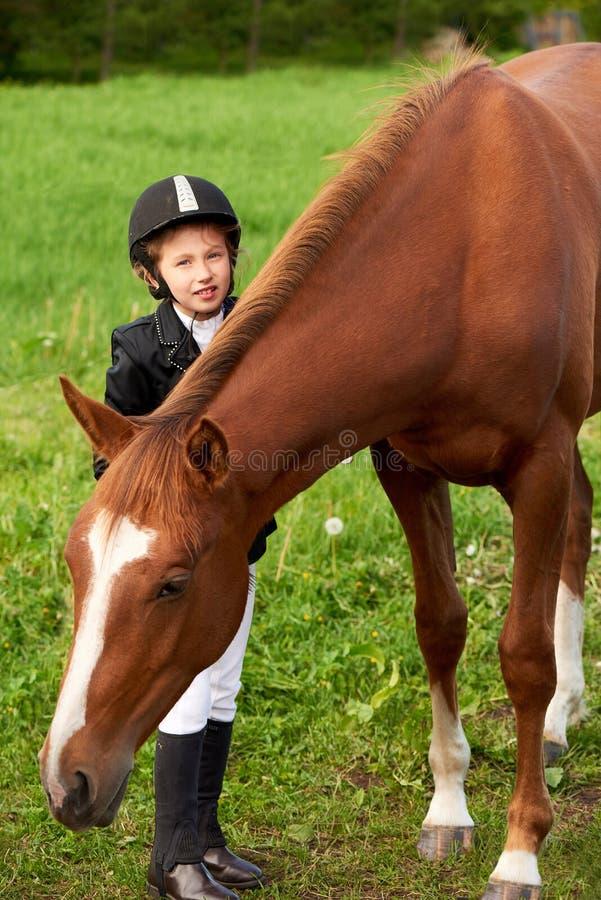 Jockey μικρών κοριτσιών παρευρίσκεται και βουρτσίζοντας το άλογό της στοκ φωτογραφία