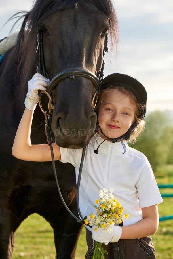 Jockey μικρών κοριτσιών που επικοινωνεί με τα άλογά της στην επαγγελματική εξάρτηση στοκ φωτογραφία με δικαίωμα ελεύθερης χρήσης
