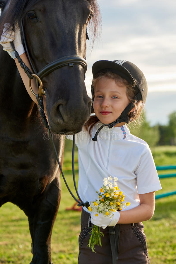 Jockey μικρών κοριτσιών που επικοινωνεί με τα άλογά της στην επαγγελματική εξάρτηση στοκ εικόνες