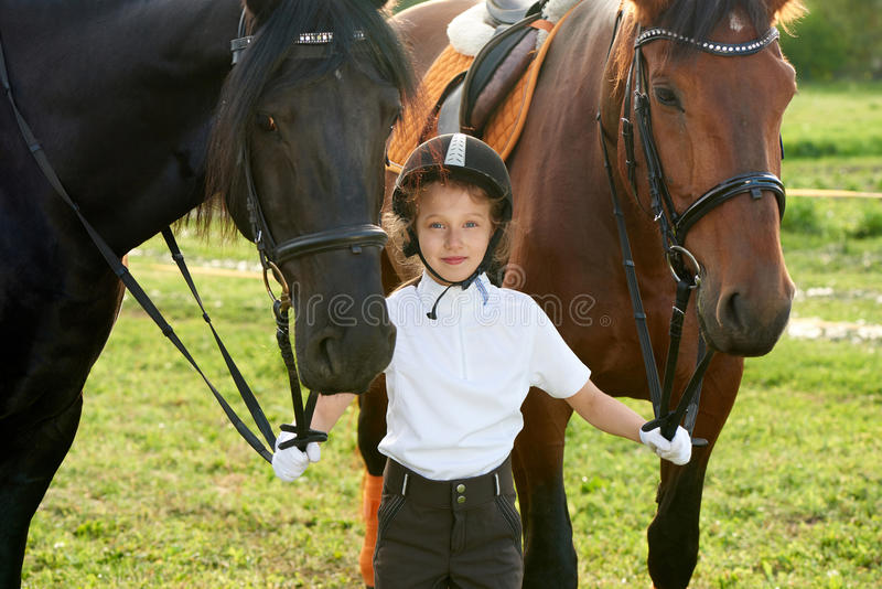 Jockey μικρών κοριτσιών που επικοινωνεί με τα άλογά της στην επαγγελματική εξάρτηση στοκ εικόνες με δικαίωμα ελεύθερης χρήσης