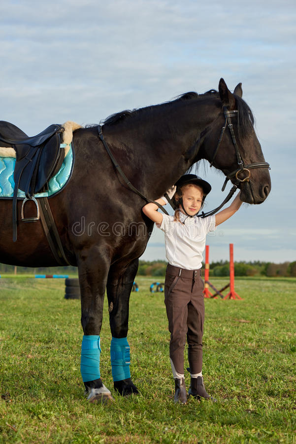 Jockey μικρών κοριτσιών που επικοινωνεί με το μαύρο άλογό της στην επαγγελματική εξάρτηση στοκ φωτογραφίες