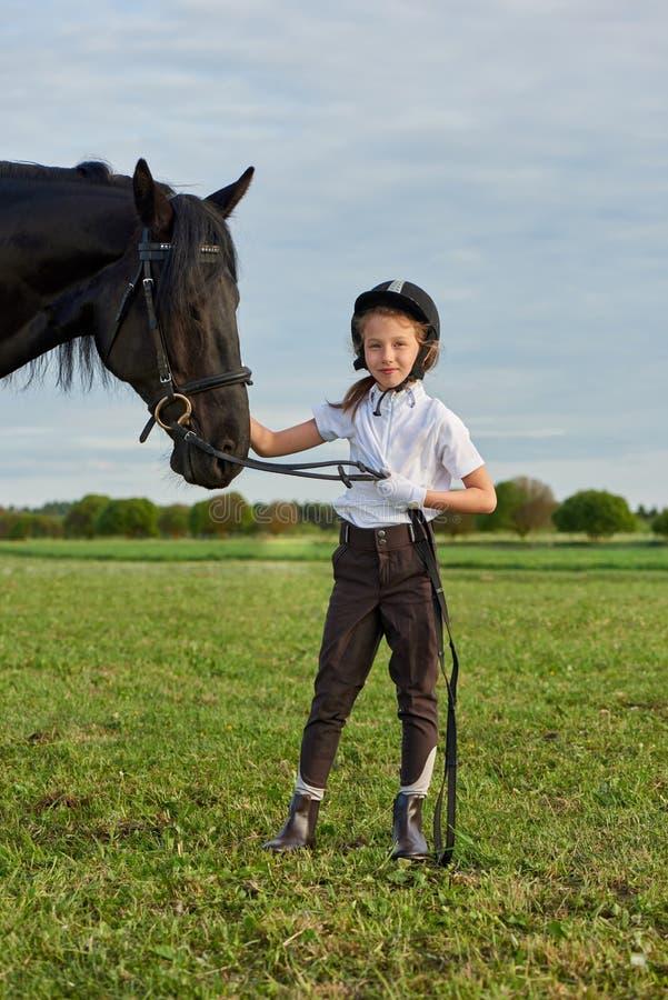 Jockey μικρών κοριτσιών που επικοινωνεί με το μαύρο άλογό της στην επαγγελματική εξάρτηση στοκ φωτογραφία