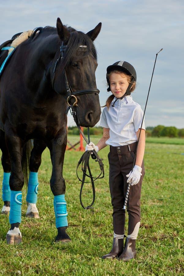 Jockey μικρών κοριτσιών που επικοινωνεί με το μαύρο άλογό της στην επαγγελματική εξάρτηση στοκ εικόνα