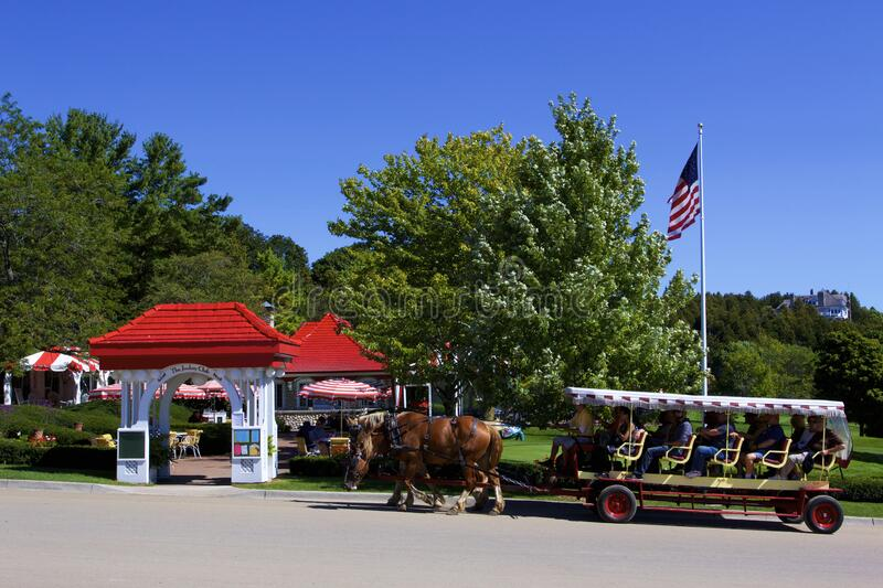 The Jockey Club  838391. Horses and Carriage passing The Jockey Club entrance at the Grand Stand on Mackinac Island Michigan  838391 stock photos