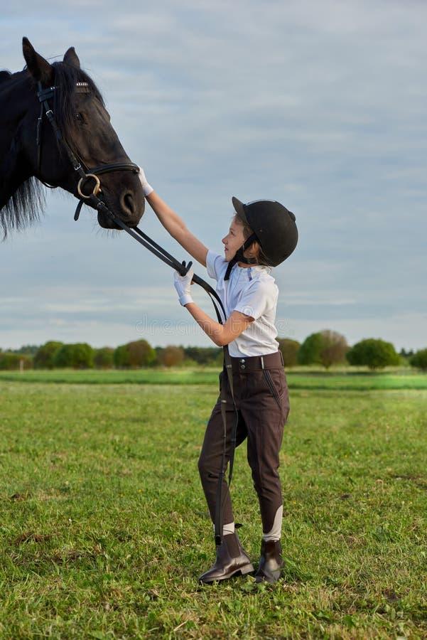 Jockey de petite fille communiquant avec son cheval noir dans l'équipement professionnel photos stock