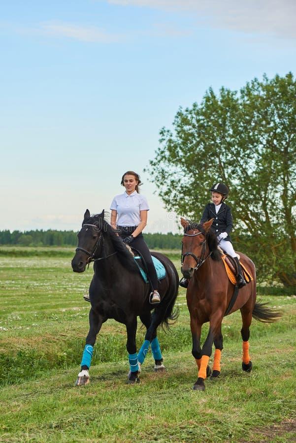 Jockey de petite fille et son entraîneur débarrassant un cheval photographie stock
