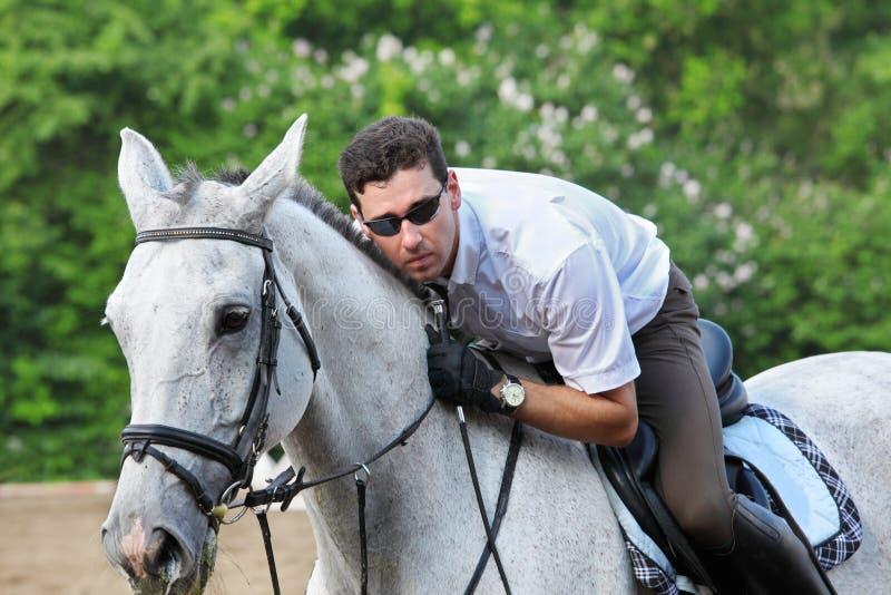 Jockey in den Gläsern mit Peitscheumarmungpferd stockbilder