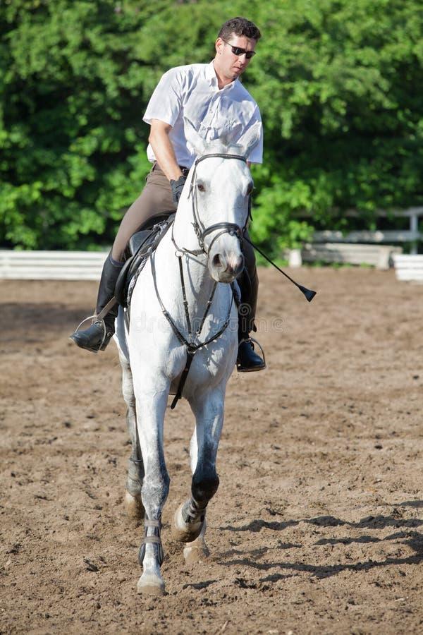Jockey in glasses riding horse stock photos