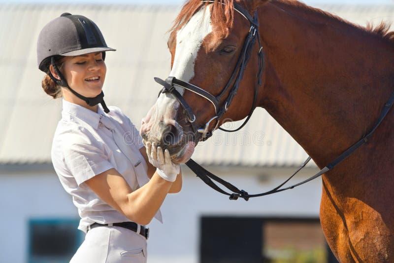 Jockey with purebred horse. Image of female jockey with purebred horse outdoors stock image