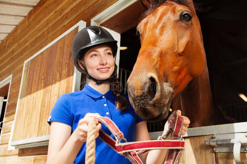 Jockeyflickan som sätter halteren på hennes fjärdhäst, tystar ned royaltyfri fotografi