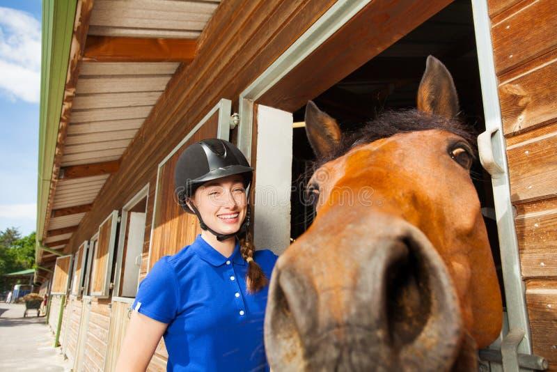 Jockeymeisje die met haar grappig paard camera bekijken stock foto