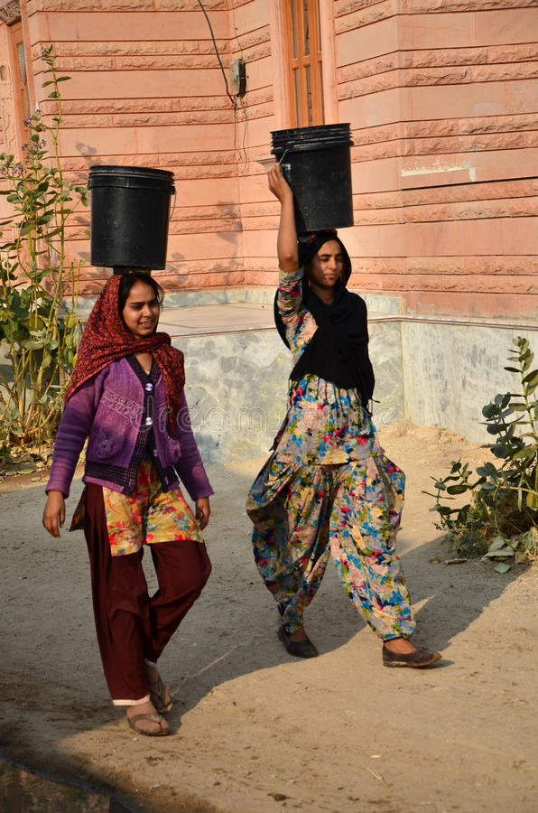 Jodhpur India, Styczeń, - 1, 2015: Indiańskie kobiety iść dla wody wioska wewnątrz dobrze zdjęcie stock